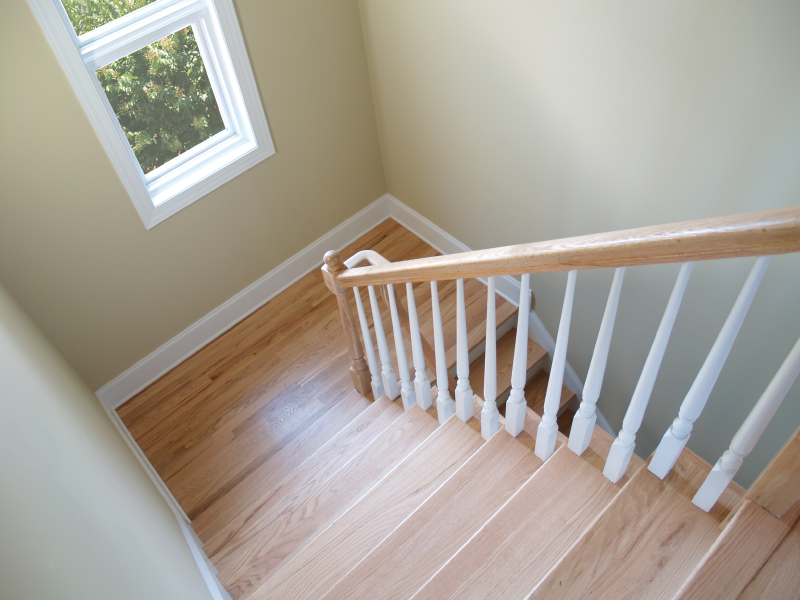 View down a wooden stairwell with a window. File includes clipping path to remove foliage outside window.